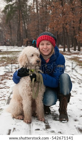 Woman squatting in an embrace with a large white poodle dog on the background of the winter forest