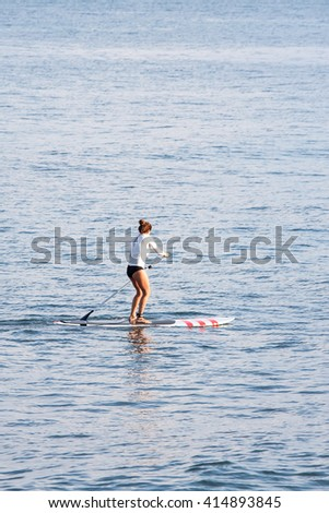 woman stand up paddle board doing sport exercise