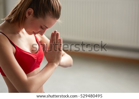 Woman standing a grateful namaste yoga pose indoors with copy space