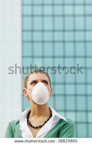 woman standing against office building and wearing protective mask. Copy space