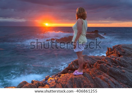 Woman standing against the rising sun at rocky coastline sunrise during your holiday on Greek coast of Aegean sea with holy mountain Athos in background. - stock photo