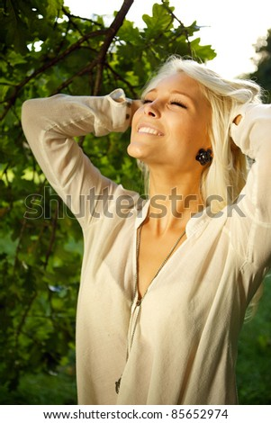 Woman standing amongst trees and enjoying the moment. - stock photo
