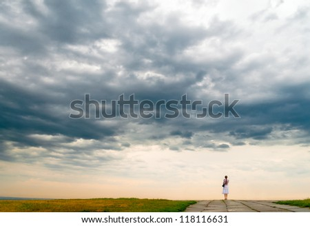 Woman standing at precipice and cloudy sky - stock photo