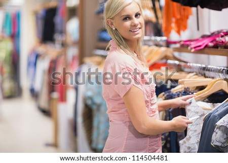 Woman standing at the clothes rack and smiling in shopping mall - stock photo