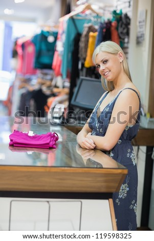 Woman standing at the counter with folded clothes and smiling - stock photo