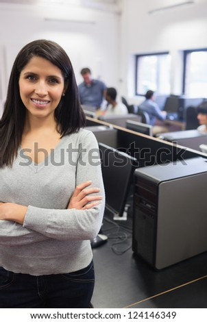 Woman standing at the front of the computer class and smiling - stock photo