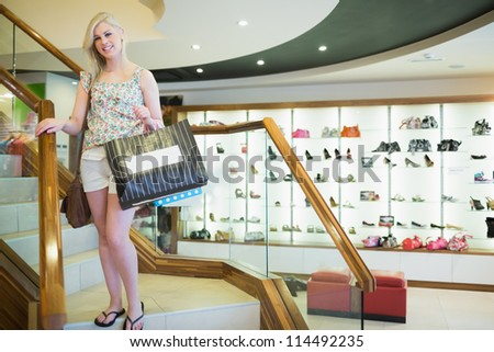 Woman standing at the stairs of a shopping mall - stock photo