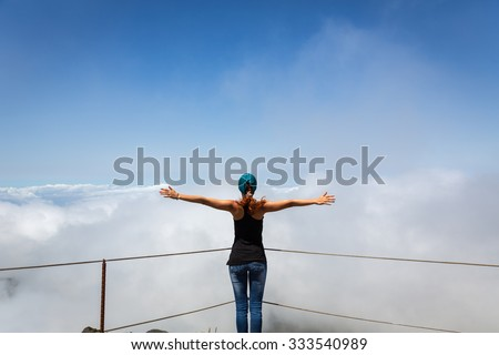 Woman standing back on cloudy mountain peak, Portugal, Madeira - stock photo
