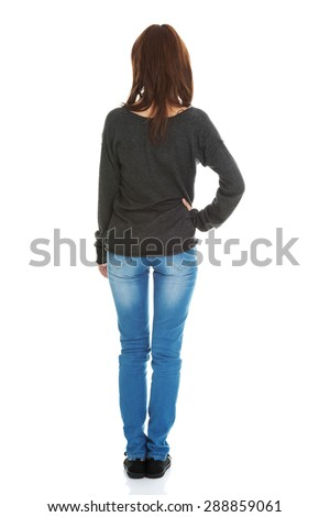 Woman standing backside with a hand on a hip - stock photo