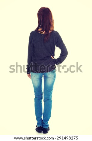 Woman standing backside with a hand on a hip