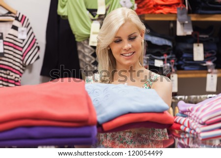 Woman standing behind a shelf in a boutique - stock photo