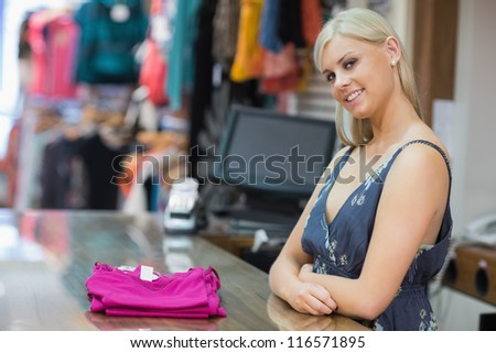 Woman standing behind the counter smiling with clothes folded on the counter - stock photo