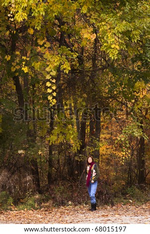 Woman standing beneath some colorful trees. - stock photo