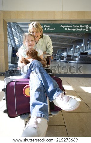 Woman standing beside luggage trolley in airport, daughter sitting on suitcase with soft toy, smiling, front view, portrait - stock photo