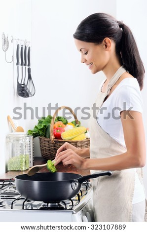 Woman standing by the stove in the kitchen, cooking and adding raw ingredients into the pot