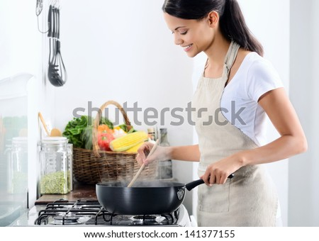 Woman standing by the stove in the kitchen, cooking and smelling the nice aromas from her meal in a pot - stock photo