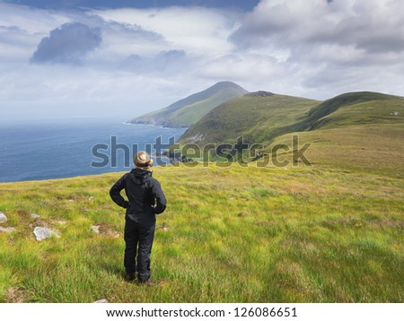Woman standing close to the coastline on Achill Island, Ireland, looking out over the sea.