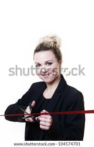 woman standing cutting ribbon with a pair of scissors