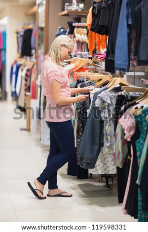 Woman standing in a shop searching for clothes - stock photo