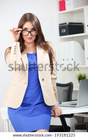 woman standing in blue dress and jacket at office