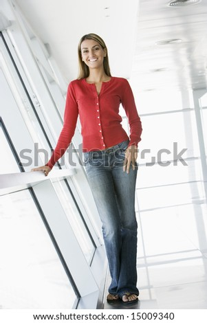 Woman standing in corridor smiling - stock photo