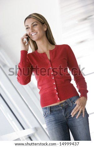 Woman standing in corridor using cellular phone smiling - stock photo