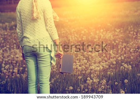 Woman standing in dandelion field with a book - stock photo