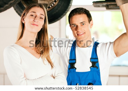 Woman standing in front of her car which is lifted on an auto hoist, a mechanic doing a repair underneath the auto