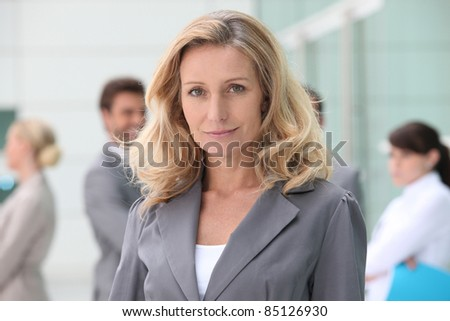 Woman standing in front of her colleagues - stock photo
