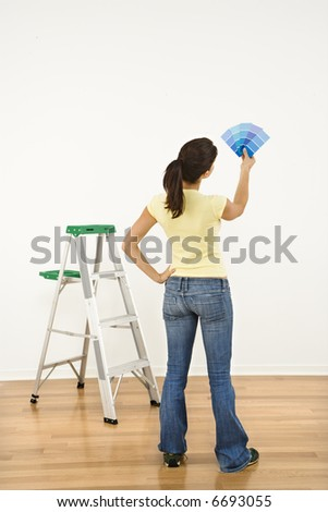 Woman standing in front of white interior wall with paint sample cards trying to choose color.