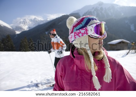 Woman standing in snow with mountains in background