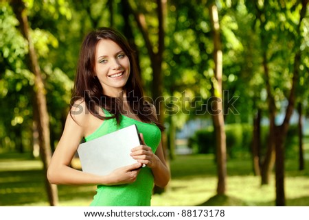 woman standing in summer park and holding laptop, copy space