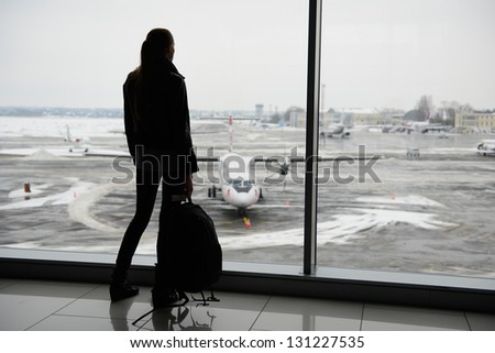 Woman standing in the airport terminal - stock photo