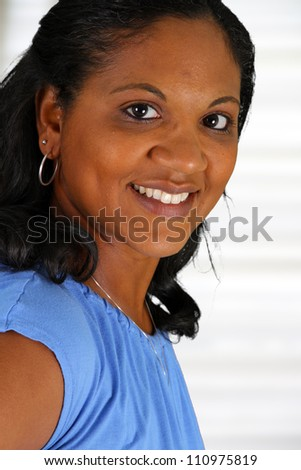 Woman standing in the living room of her home - stock photo