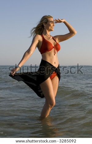 Woman standing in the water, looking ahead.  Oceans and sky in the background - stock photo