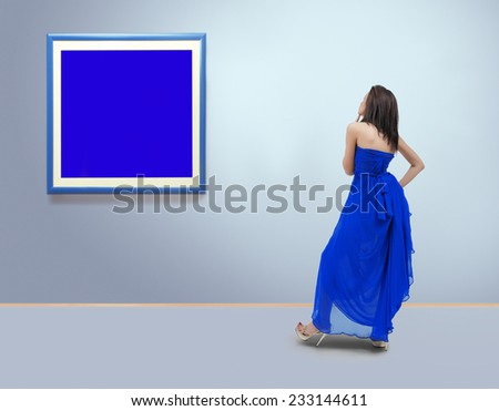 Woman standing inside a gallery in front of blank  picture frames.Film grain is added for better impression - stock photo