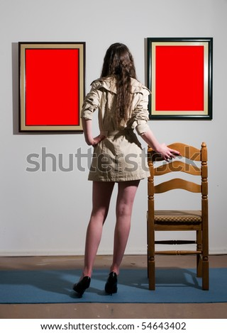 Woman standing inside a gallery infront of two picture frames and looking at them. - stock photo