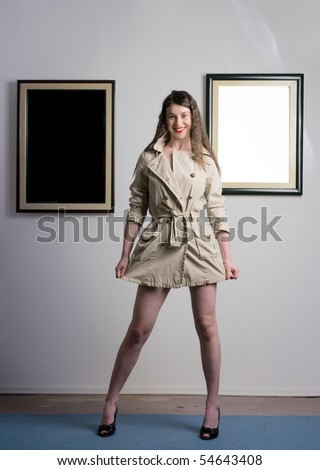 Woman standing inside a gallery infront of two picture frames with smile on her face. - stock photo