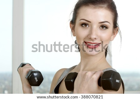 Woman standing is doing exercise using dumbbells for biceps. Concept: lifestyle, fitness, aerobics and health.
