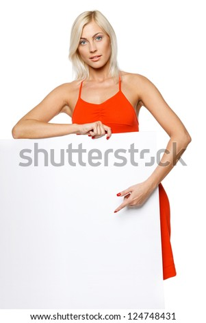 Woman standing leaning at empty whiteboard, pointing at it, over white background - stock photo