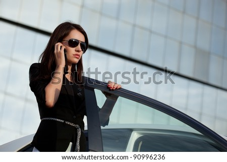 woman standing near car and calling by phone - stock photo