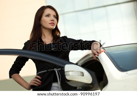 woman standing near car, bottom point of view - stock photo