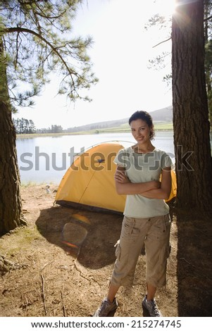 Woman standing near tent on lakeside camping trip, arms folded, smiling, portrait (lens flare) - stock photo