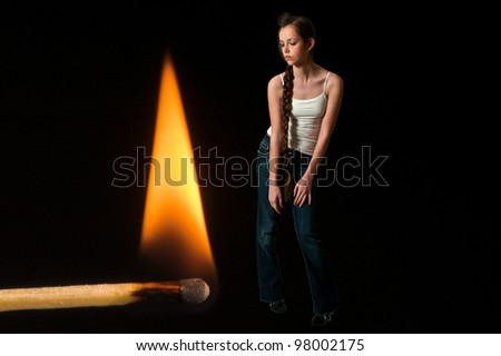 Woman standing next to a burning match - stock photo