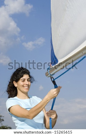 Woman standing next to sailboat tying rigging to sail. Vertically framed photo - stock photo