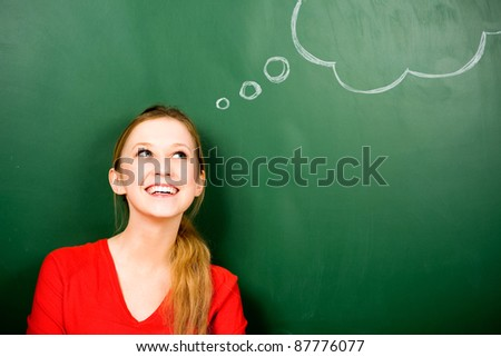 Woman standing next to thought bubble on blackboard - stock photo