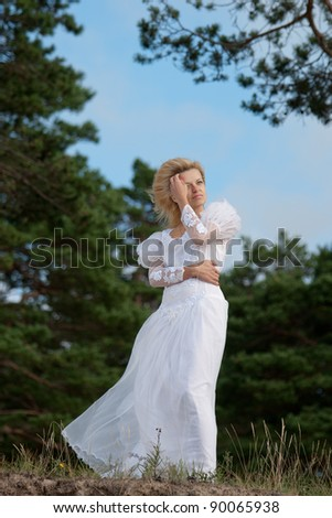 Woman standing on a cliff in a long white dress and looking into the horizon - stock photo
