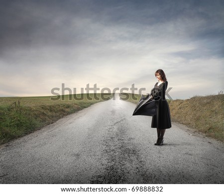 Woman standing on a countryside road and opening an umbrella