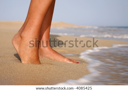 Woman standing  on a golden beach with waves at her feet