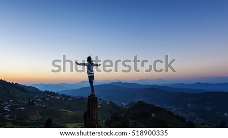 Woman standing on a large tree in front of a sunset and mountain view around.